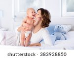 mother and child on a white bed.... | Shutterstock . vector #383928850