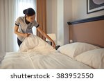 young maid arranging blanket on ... | Shutterstock . vector #383952550