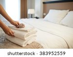 Stock photo hands of hotel maid putting flowers on the stack of towels 383952559