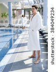 Small photo of Man standing next to a pool in a robe and relaxing