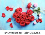Stock photo fresh red roses buds in shape of heart on blue wooden background 384083266