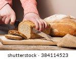 woman slicing mixed grain bread ... | Shutterstock . vector #384114523