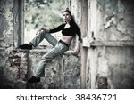 Young woman smoking in a ruined building. Contrast colors. - stock photo