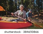 Portrait of happy senior woman in a kayak holding paddles. Woman canoeing with man in background on the lake. - stock photo