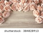 Stock photo border of pink roses on a wooden background with empty space for text top view with copy space 384828913