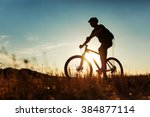man cyclist with bike on sunset | Shutterstock . vector #384877114
