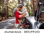 Stock photo young and lovely couple in sweates and hats having fun hugging together near the car on the 385199143