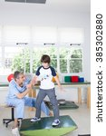 male therapist with boy in rehab   Shutterstock . vector #385302880