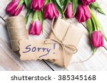 Small photo of word SORRY and bouquet of tulips on wooden background