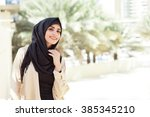smiling girl in hijab covering... | Shutterstock . vector #385345210
