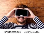Stock photo man wearing virtual reality goggles studio shot wooden background 385433683