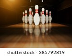 Small photo of Ten white pins in a bowling alley lane
