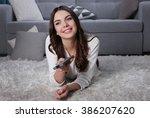young beautiful woman watching... | Shutterstock . vector #386207620