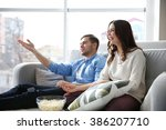 young couple watching tv on a... | Shutterstock . vector #386207710