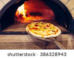 pizza cooking in a traditional... | Shutterstock . vector #386328943