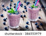 blueberry smoothie in a glass... | Shutterstock . vector #386553979