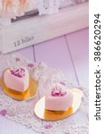Small photo of Heart shaped mini mousse cakes covered with pink chocolate velour on pastel colored shabby chic background. Romantic modern european cake for valentines day. Shallow focus