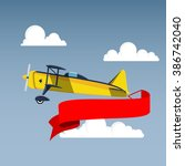 airplane with banner in the sky | Shutterstock .eps vector #386742040