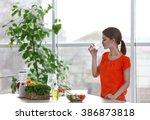 young woman drinking water near ... | Shutterstock . vector #386873818