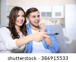young couple watching tv on a... | Shutterstock . vector #386915533