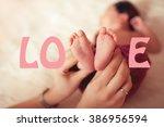 woman holding baby feet closeup.... | Shutterstock . vector #386956594