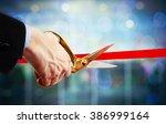 Businessman cutting red ribbon...