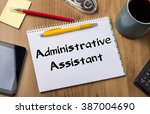 Small photo of Administrative Assistant - Note Pad With Text On Wooden Table - with office tools