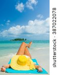 woman lies on the beach with... | Shutterstock . vector #387022078