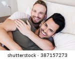 happy gay couple lying on bed... | Shutterstock . vector #387157273
