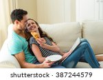 young couple having croissant... | Shutterstock . vector #387244579