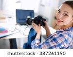 female photographer sitting on... | Shutterstock . vector #387261190