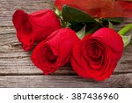 Red Roses Over Wooden Table