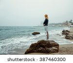Young girl standing alone on a rock near the coast of the sea / ocean. Fresh spring morning, and a dramatic sky.