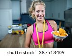 fit woman showing a bowl of... | Shutterstock . vector #387513409