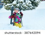 happy kid sitting in snow with... | Shutterstock . vector #387642094