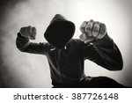 Small photo of Street aggression, being punched and mugged by violent man in hooded jacket, victim's pov perspective, monochromatic image.
