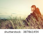 sad young girl sitting alone on ... | Shutterstock . vector #387861454
