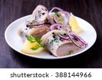 Stock photo herring with pepper herbs salt and lemon on white ceramic plate on black background 388144966