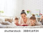 pretty young mother reading a... | Shutterstock . vector #388416934