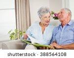 senior couple sitting on sofa... | Shutterstock . vector #388564108