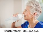 happy senior woman drinking... | Shutterstock . vector #388566466