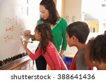 pupil writing on the board at... | Shutterstock . vector #388641436