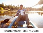 young man rowing kayak on lake | Shutterstock . vector #388712938