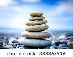 Stones pyramid on pebble beach symbolizing stability, zen, harmony, balance. Shallow depth of field.