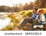 Stock photo father teaching son to fish by lake 389025814
