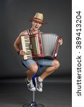 Small photo of Portrait of a man in straw hat playing on accordion