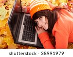 Girl in autumn orange leaves with laptop. Fall sale. Outdoor. - stock photo