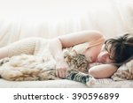Stock photo beautiful pregnant girl sleeping on a bed with a beautiful large cat 390596899