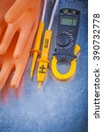 Small photo of Digital ammeter electric tester insulating rubber gloves on metallic background electricity concept.