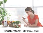 young woman drinking water near ... | Shutterstock . vector #391063453